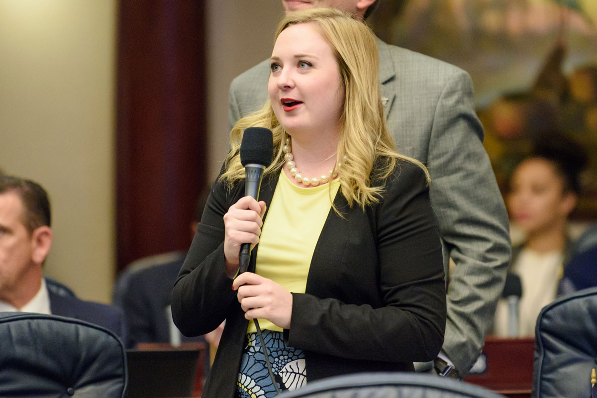 A young woman with blonde hair wearing a yellow shirt and black blazer stands holding a microphone