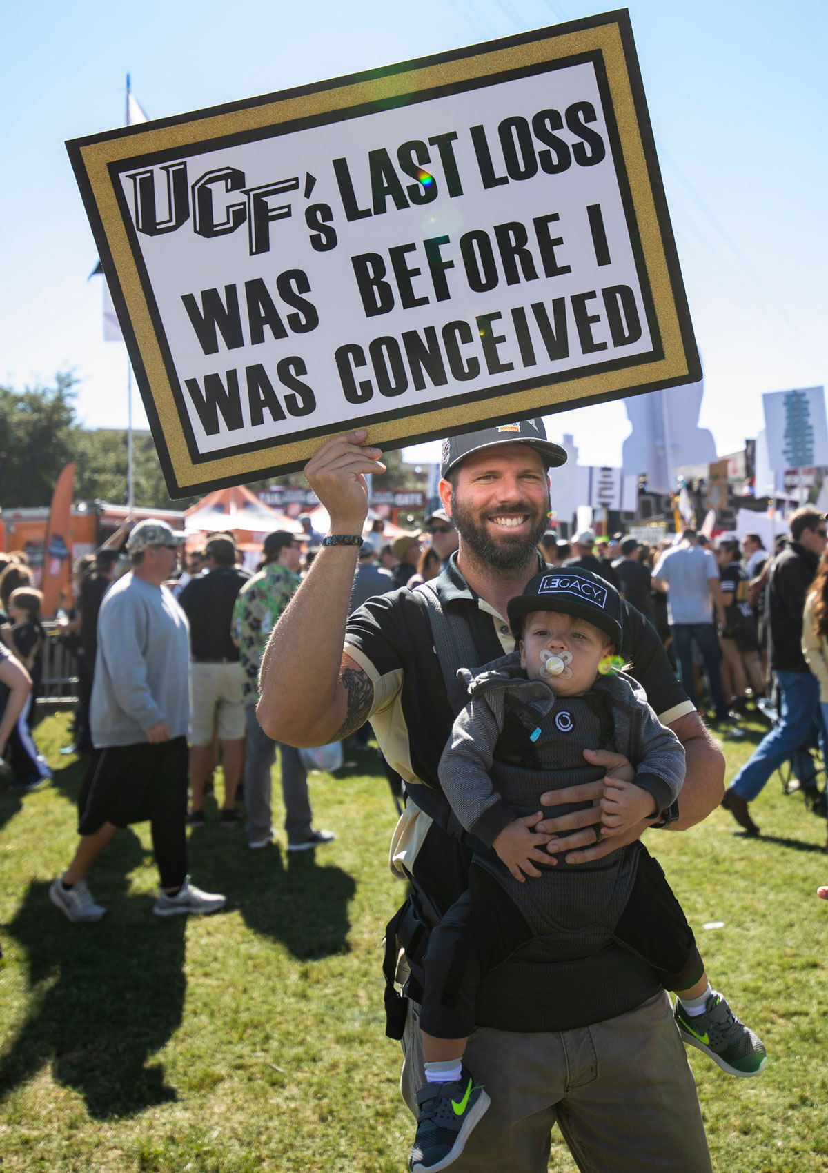 """Man holding a baby with a sign that read """"UCF's last loss was before I was conceived"""""""