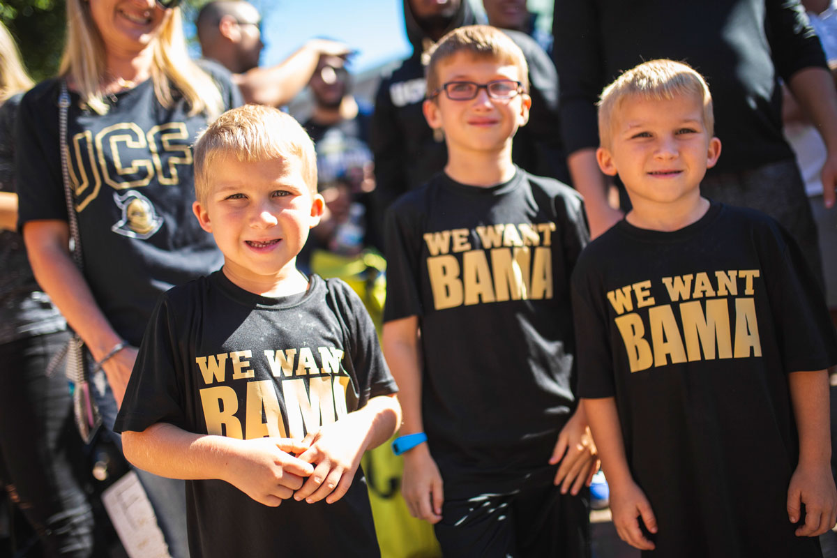 three small children wear black and gold shirts that say We Want Bama