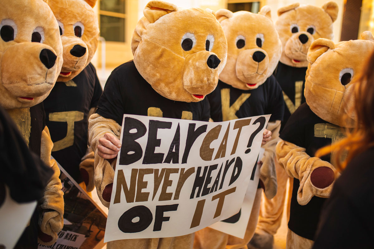 People dressed like golden color bears hold a sign that says Bearcat? Never heard of it.