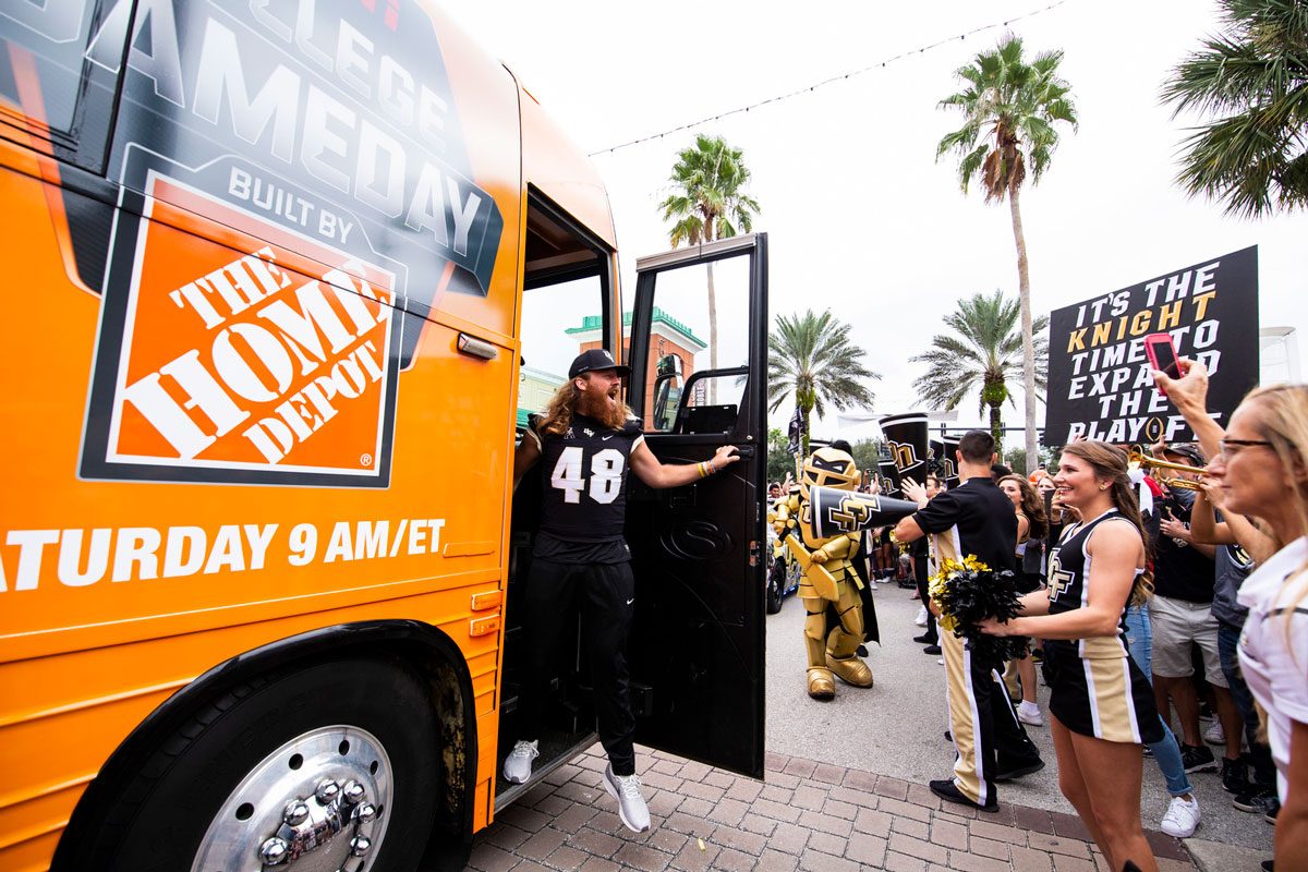 UCF Football player Mac Loudermilk wearing his #48 jersey steps off Orange bus with Home Depot logo and greets cheering fans
