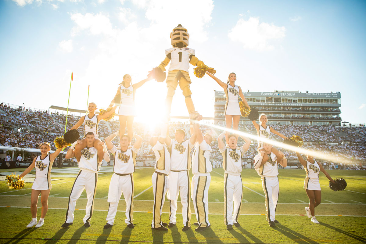 Knightro mascot stands atop a cheerleader pyramid on the football field with Spectrum Stadium crowd in the background as sun sets