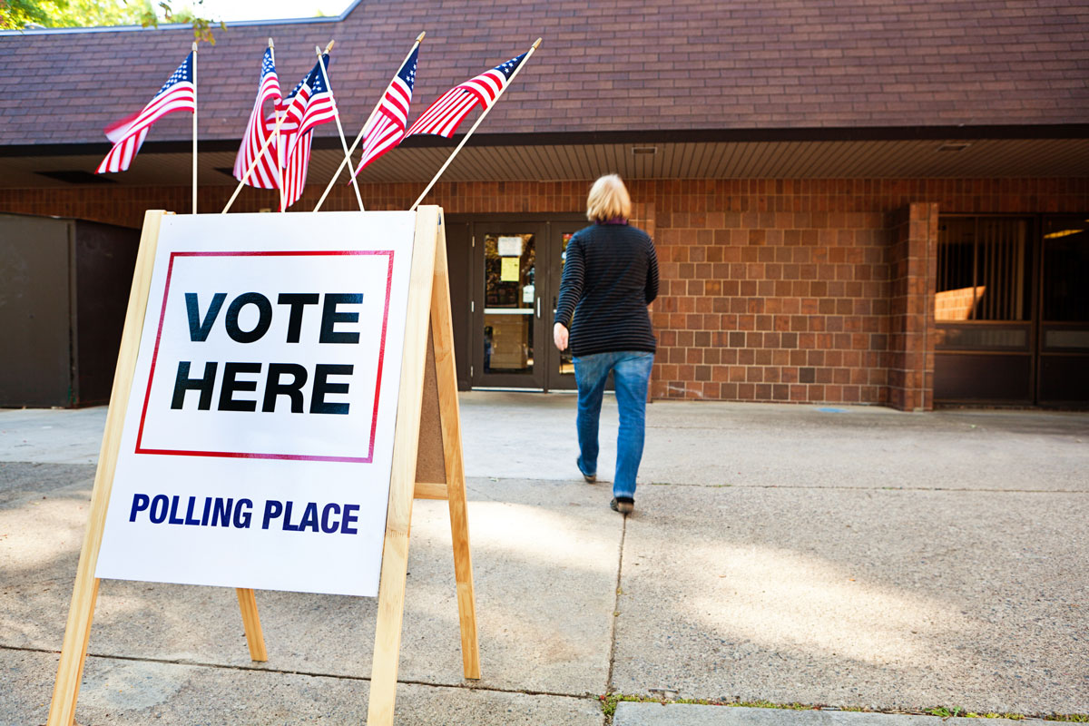 A blonde woman with a black long-sleeve shirt and jeans walks into a brick building with a sign outside that reads, Vote Here Polling Place