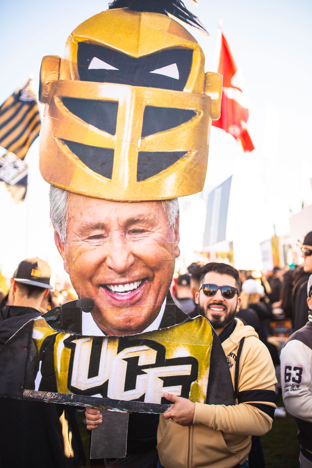 Man wearing a black and gold jersey holds a cutout of Lee Corso head with Knightro mask