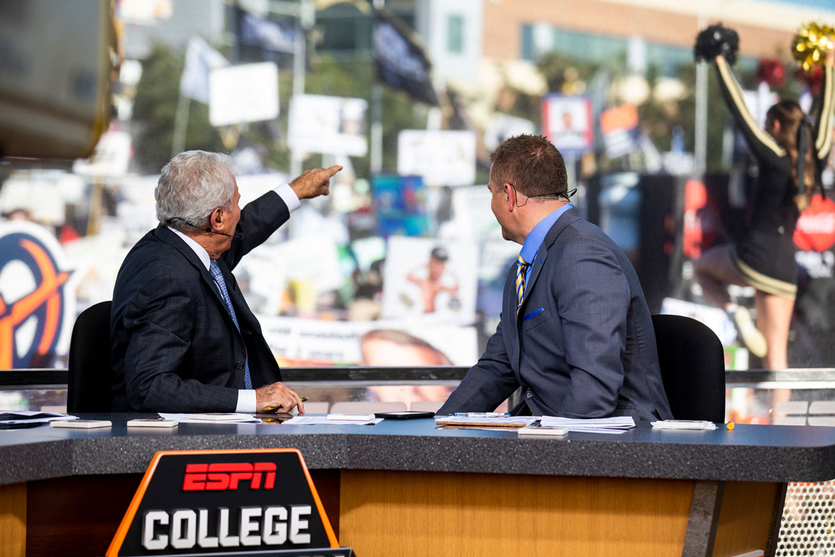 ESPN analysts Lee Corso and Kirk Herbstreit look back at the crowd from their desk chairs