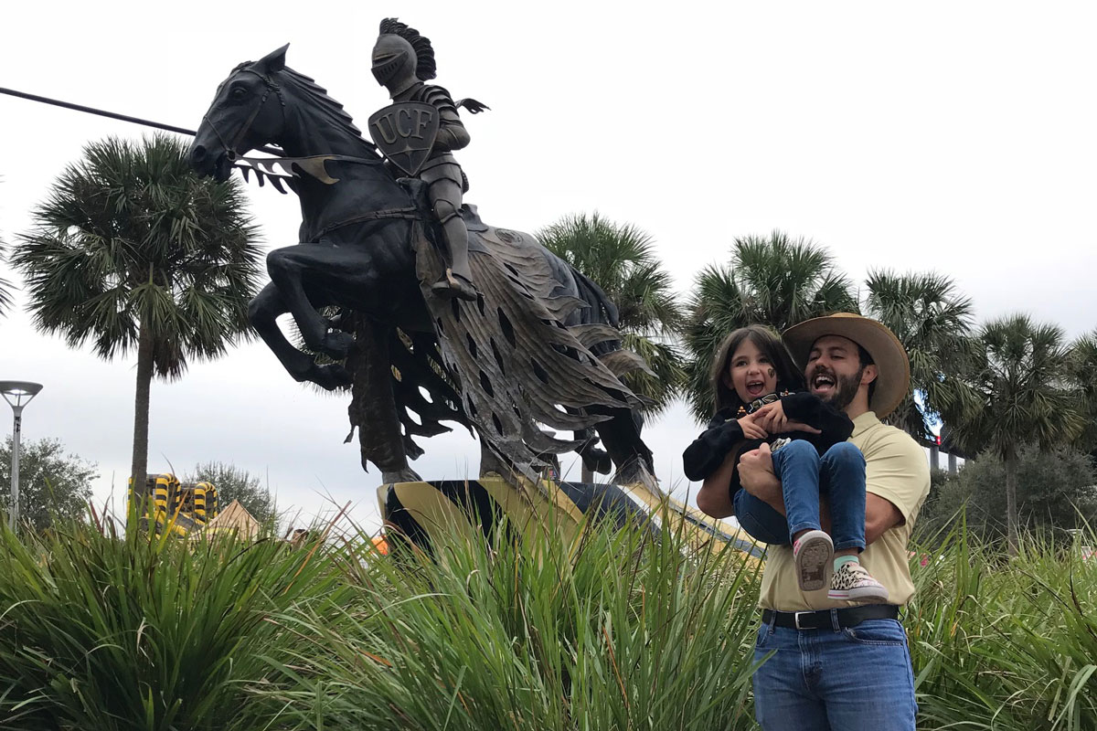 A man wearing a straw hat, yellow t shirt and blue jeans cradles a small child in front of a bronze statue of a knight holding a lance while riding a horse