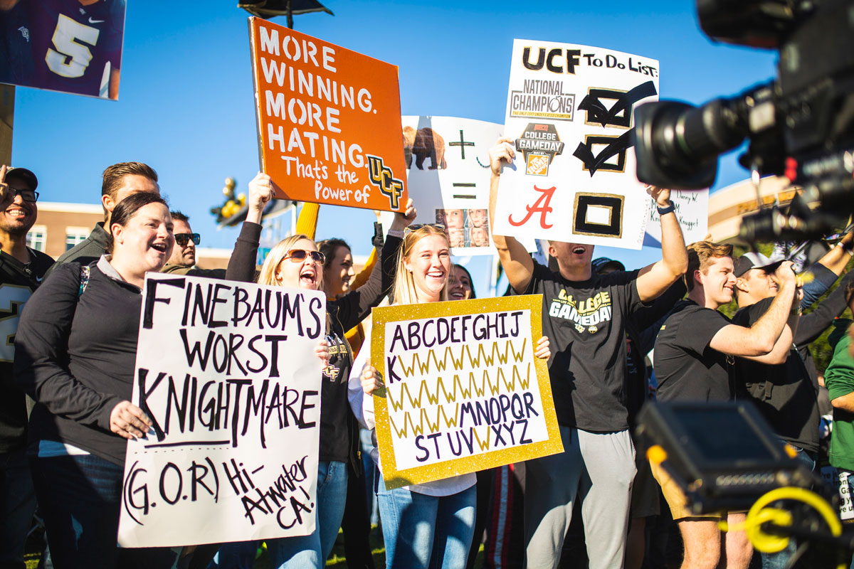 Fans holding up homemade signs about UCF Football in front of a camera lens