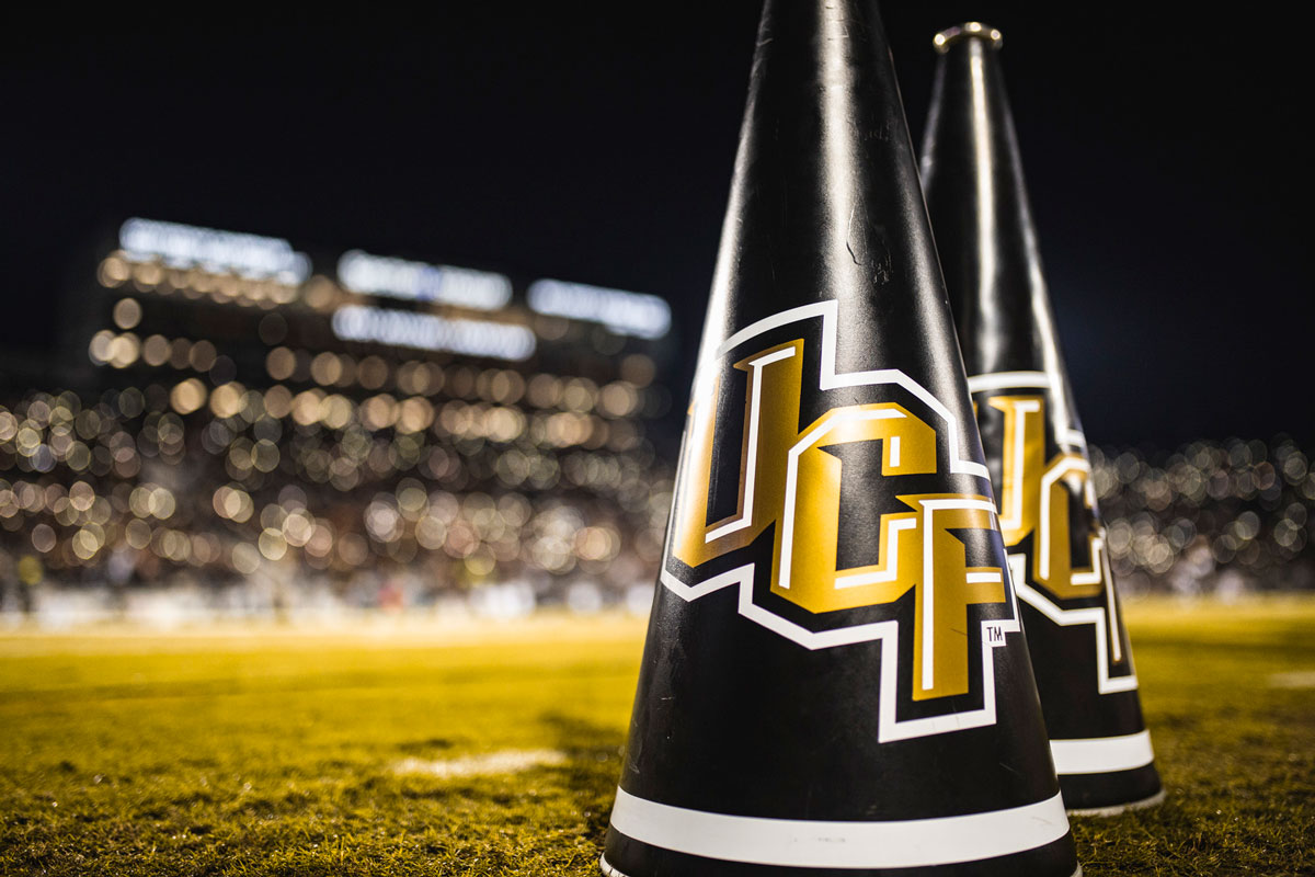 two black megaphones with UCF logo placed on grass in football stadium
