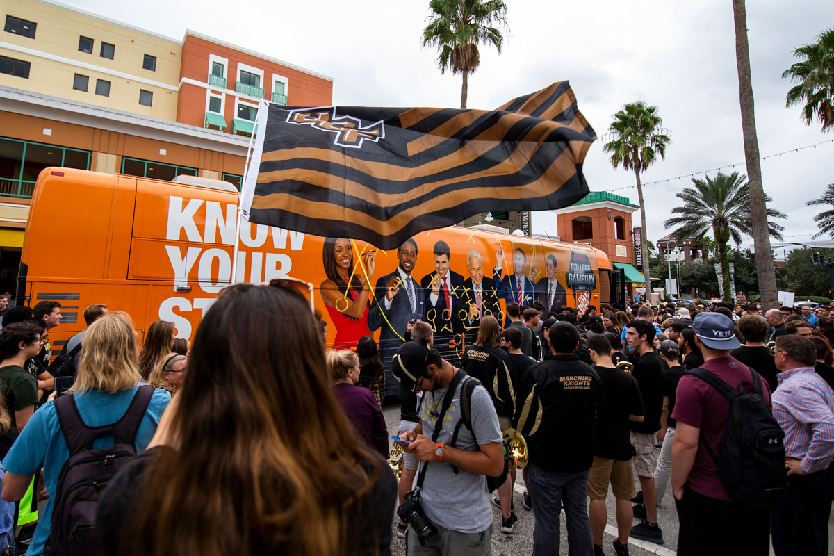 Black and Gold UCF flag waves in front of orange bus with a crowd around it