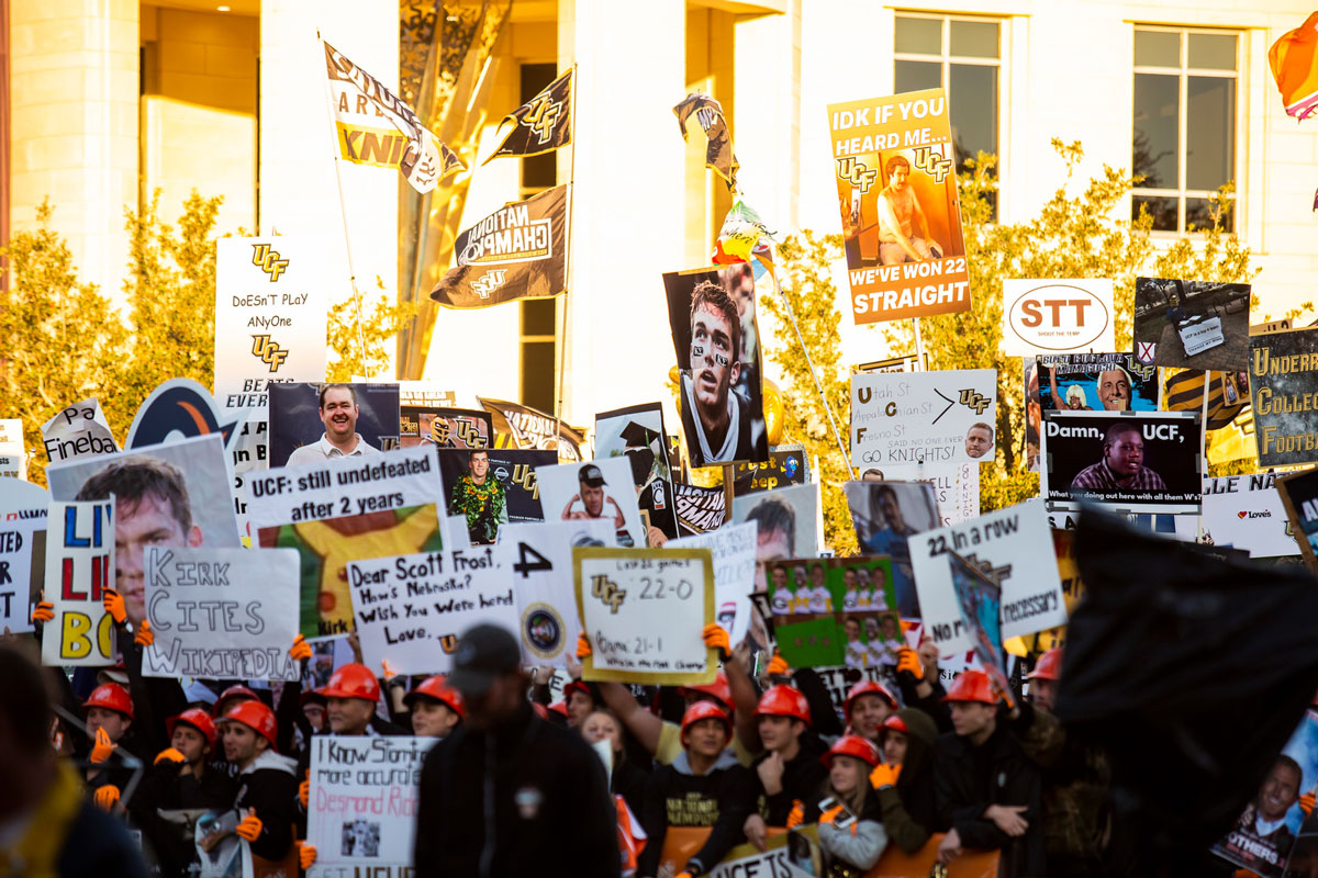 A sea of fans holding signs in front of a brick building