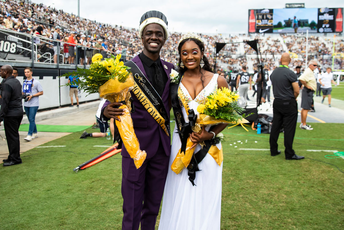 a man in a black suit wearing a king crown and a woman in a white gown both hold flowers and stand on a football field as Homecoming king and queen