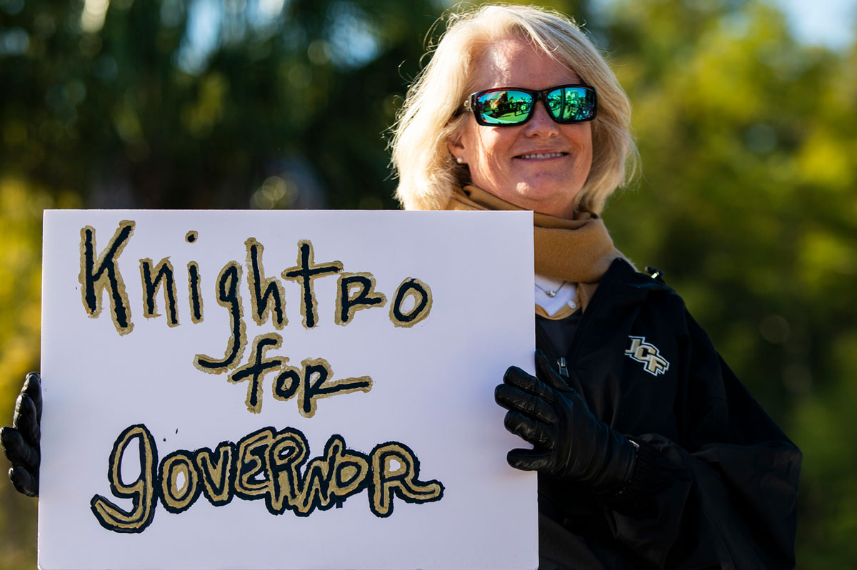 Blonde woman wearing sunglasses holds sign that says Knightro for Governor