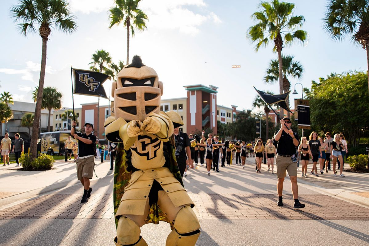 UCF mascot Knightro walks down the road with UCF cheerleaders and flags waving behind him
