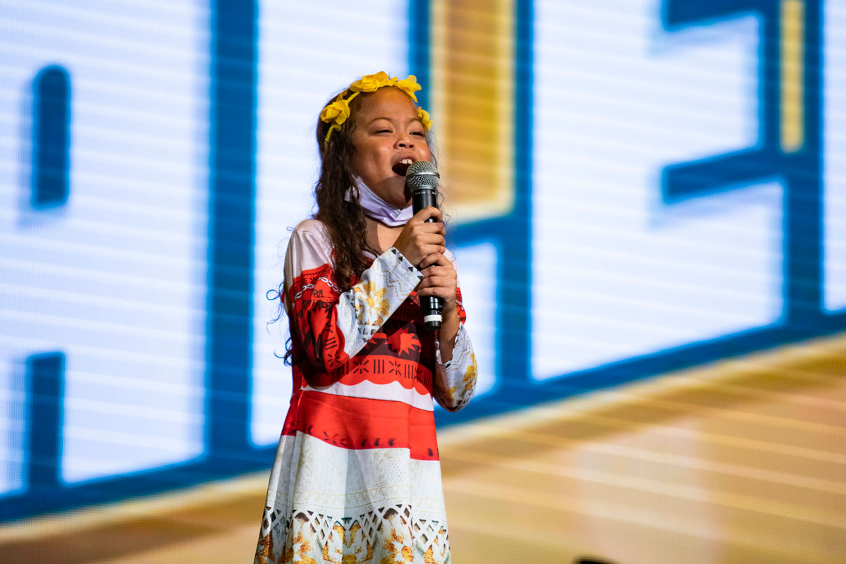 A young girl with a yellow headband and red and gray dress sings into a microphone
