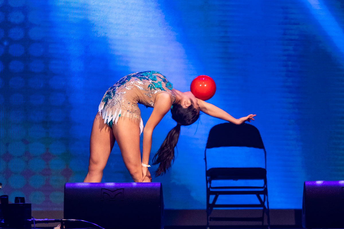 A woman with a black pony tail does a standing back bend while balancing a red ball on her outstretched arm
