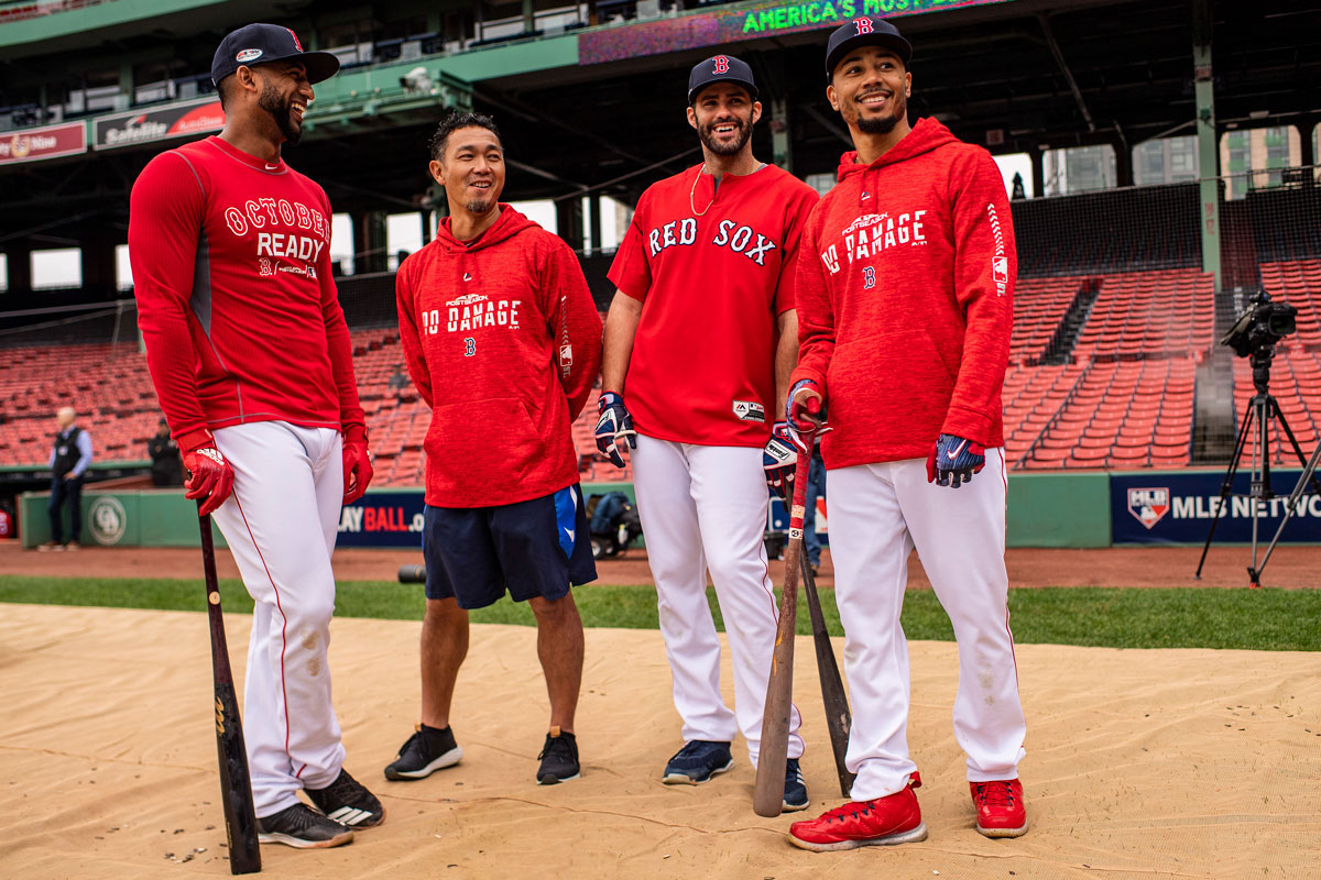 Four men in red Red Sox long sleeve shirts pose in Fenway Park