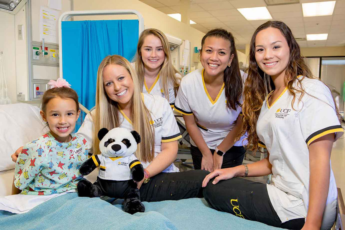 four UCF nursing students give a stuffed panda bear to a girl wearing a green gown in a hospital bed.