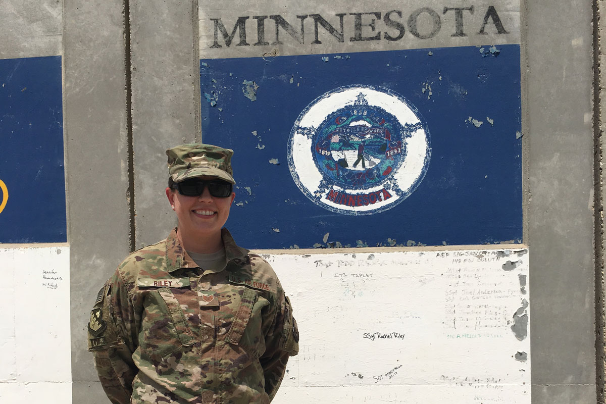 A woman in camouflage clothes and a hat and dark sunglasses stands in front of a concrete wall with Minnesota written on it