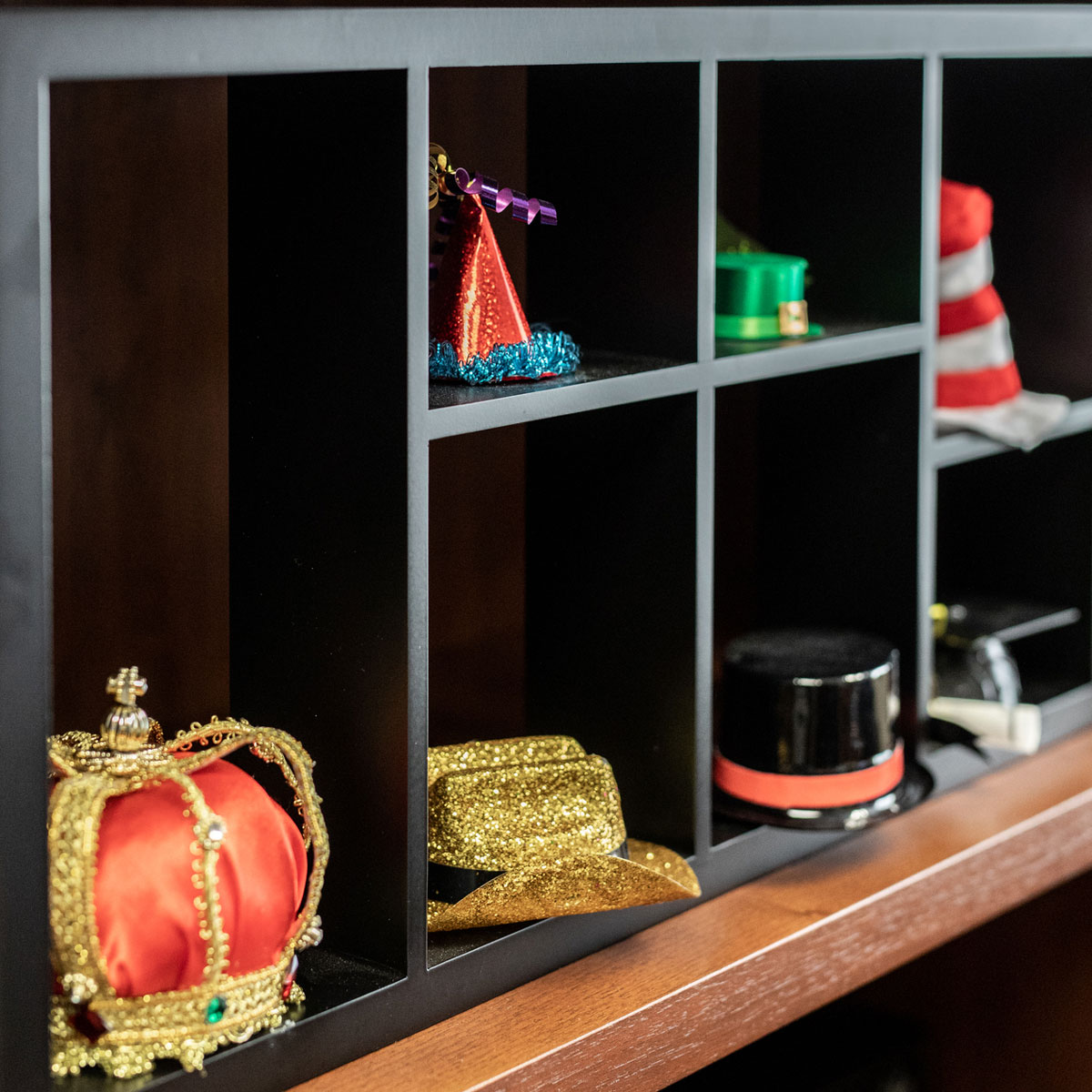 a black horizontal cube shelf with hats of different styles featuring a royal crown, cowboy hat and top hat