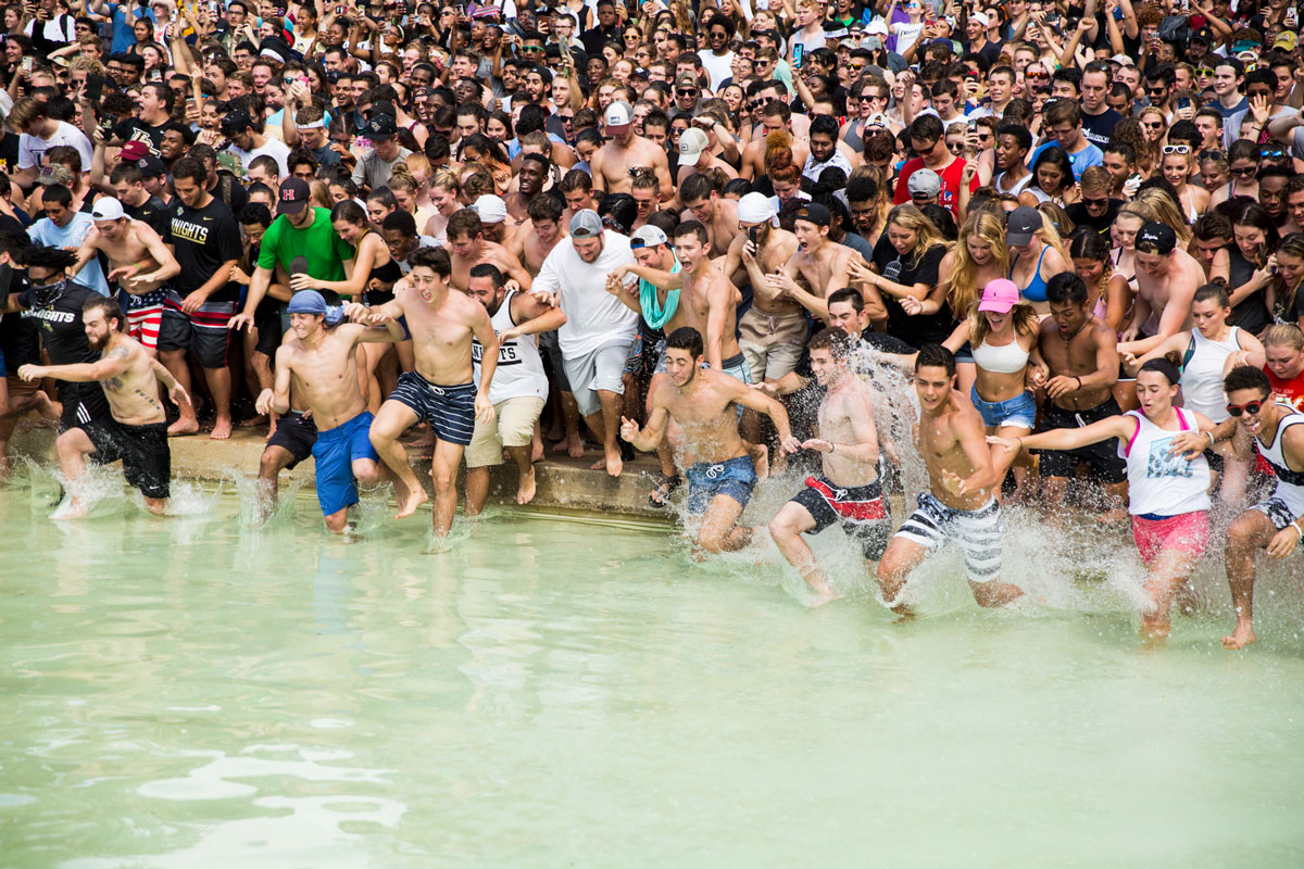 A mob of college students in bathing suits rush into a pond of water.