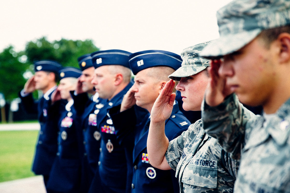 Seven men and women dressed in uniform stand at salute