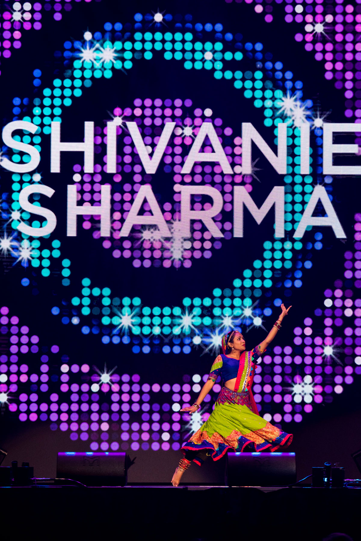 A young woman dances in front of an electronic board lit up in green and purple swirls