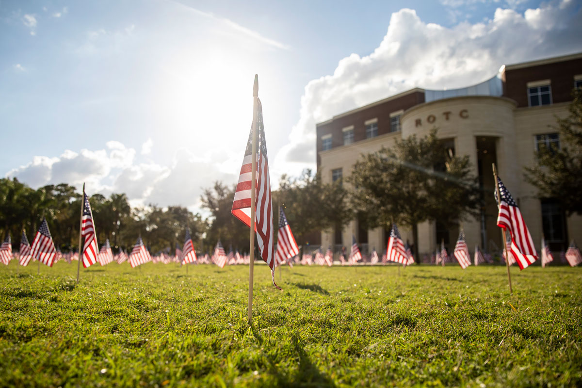 Sunny day, small American flags planted into grass with an ROTC brick building in the background