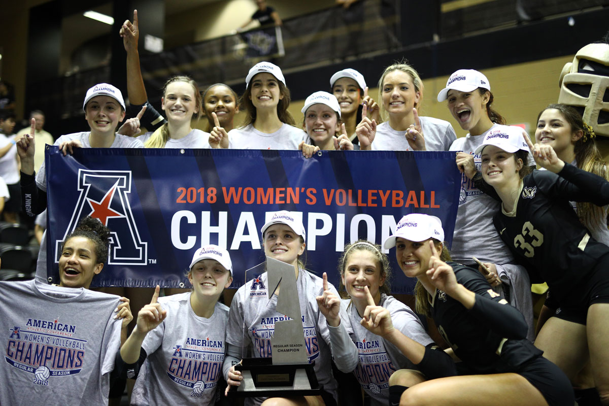 Volleyball team wearing white hats and gray t shirts pose with a silver trophy around a blue banner reading 2018 Women's Volleyball Champions