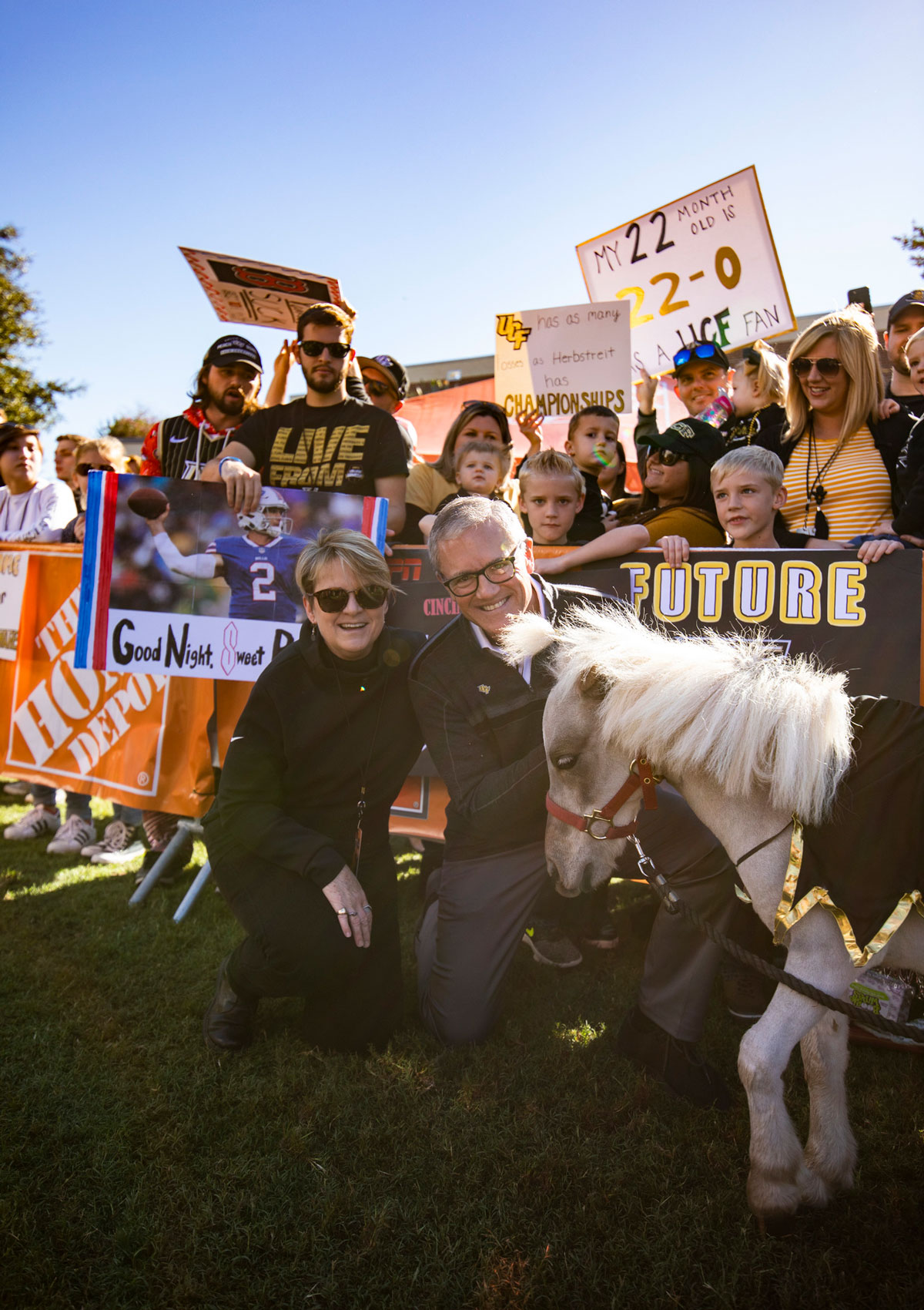 President Dale Whittaker and wife Mary kneel by mini horse Knugget in front of cheering fans