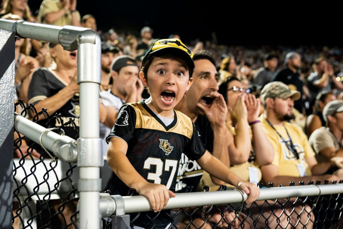 a young fan wearing a black and gold football jersey cheers in the stands