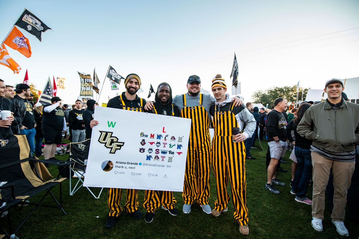 Four men wearing black and gold stripped overalls hold a sign