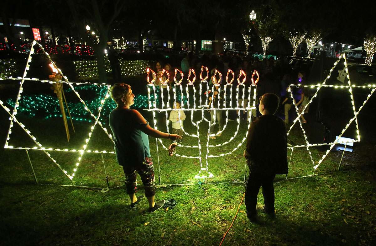 Two people look at lights shaped like a Menorah and Star of David on a grassy lot