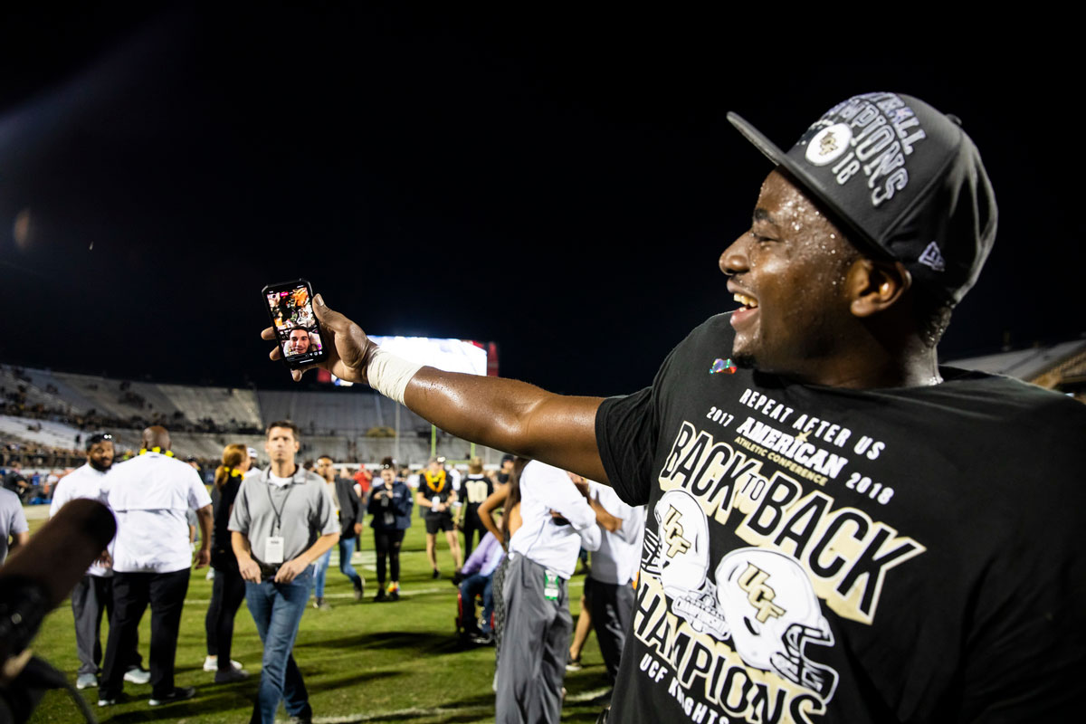 A UCF player wearing a black championship t shirt and hat holds out his arm to FaceTime McKenzie Milton