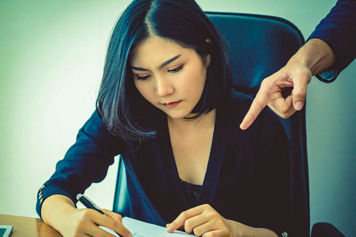A dark-haired woman sits at a desk with a pen in hand as another's hand points over her shoulder at her paper
