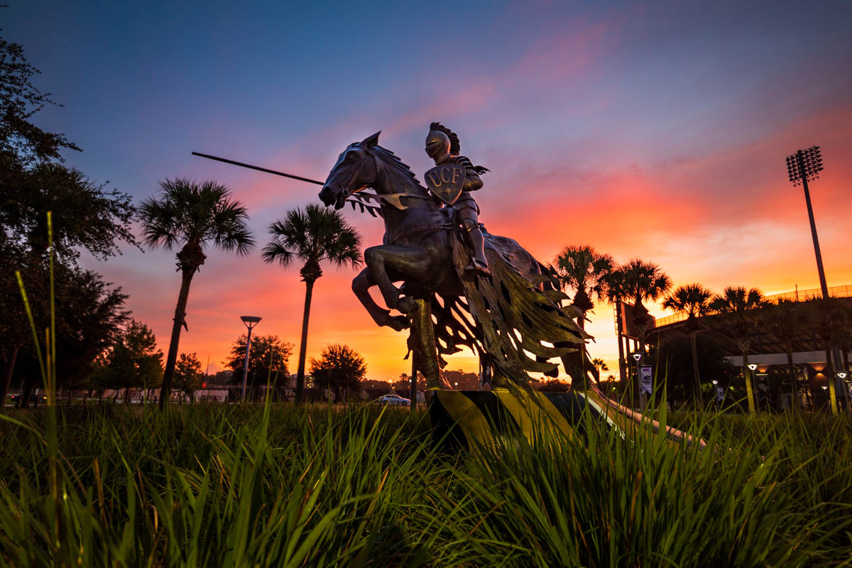 The sun rises over the Charging Knight statue outside of Spectrum Stadium.