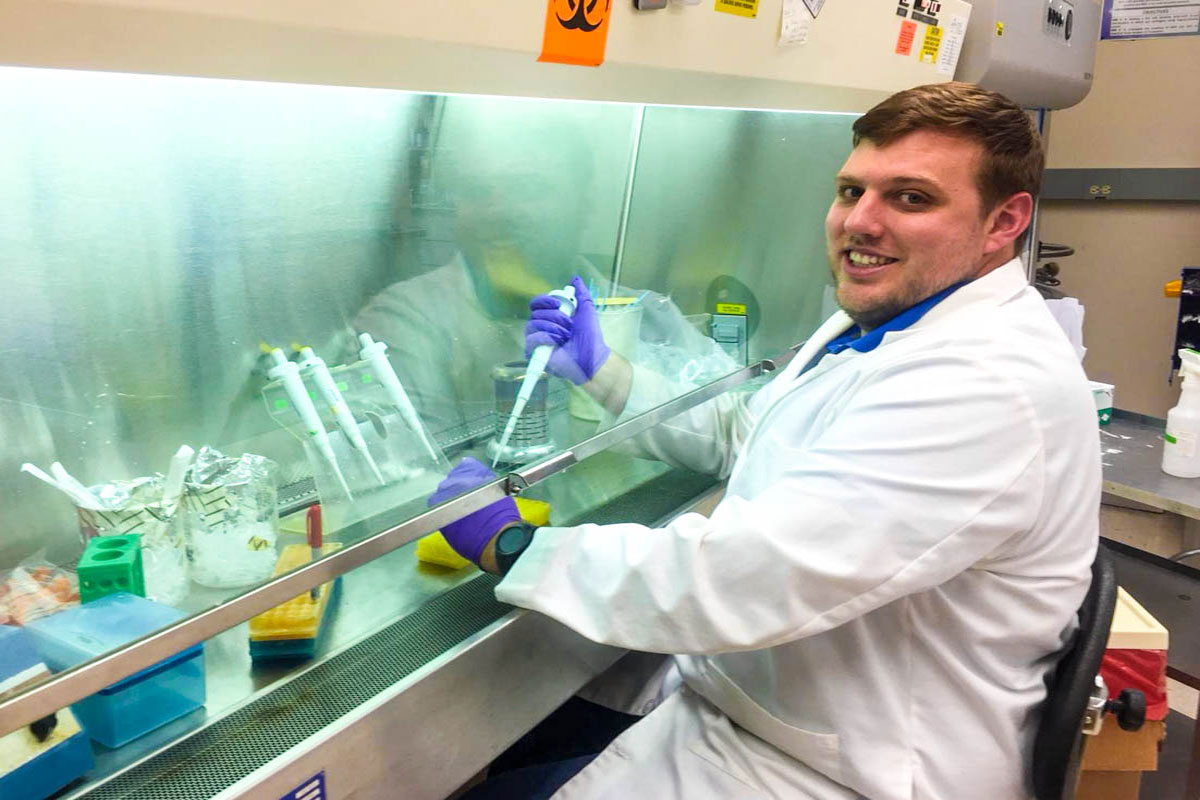 A man in a white lab coat holds a test tube