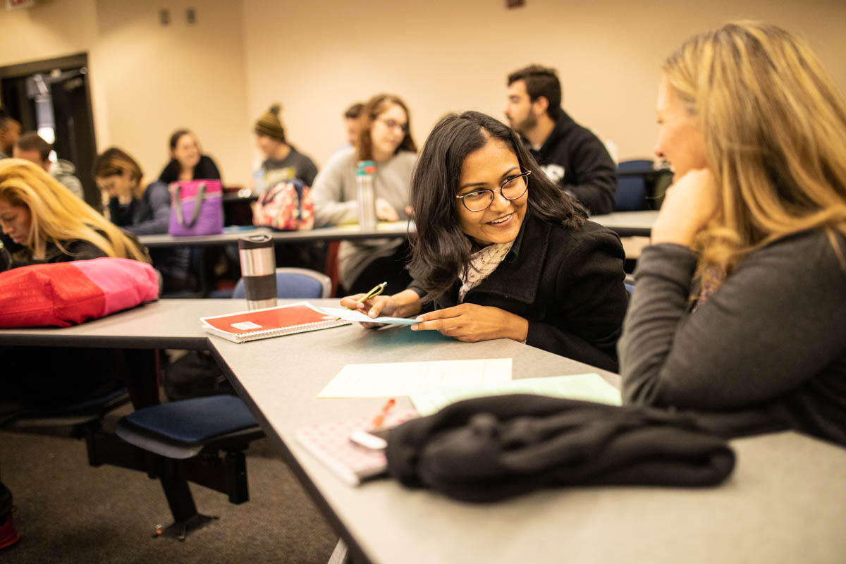 Students work together in pairs to negotiate a deal during a class. (Photo by Austin Warren)