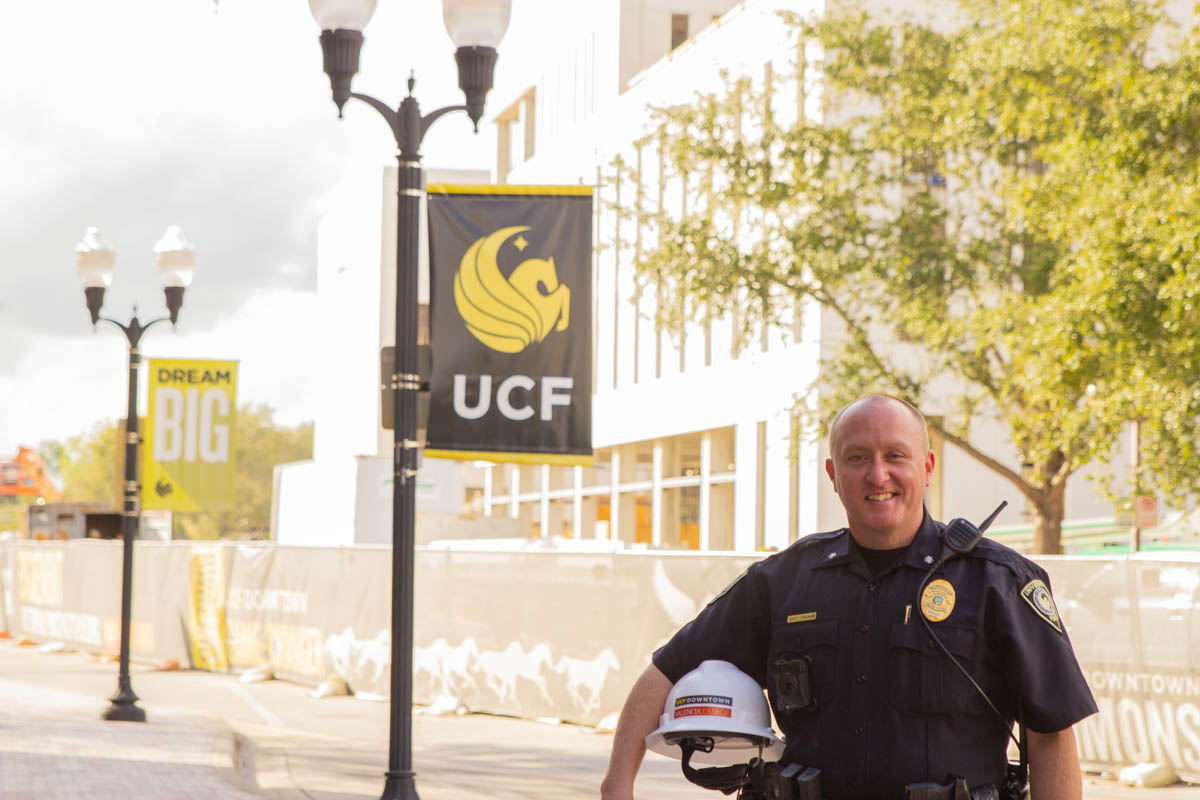 A bald man wearing a police uniform stands outside in front of a light pole with a UCF banner and building in the background