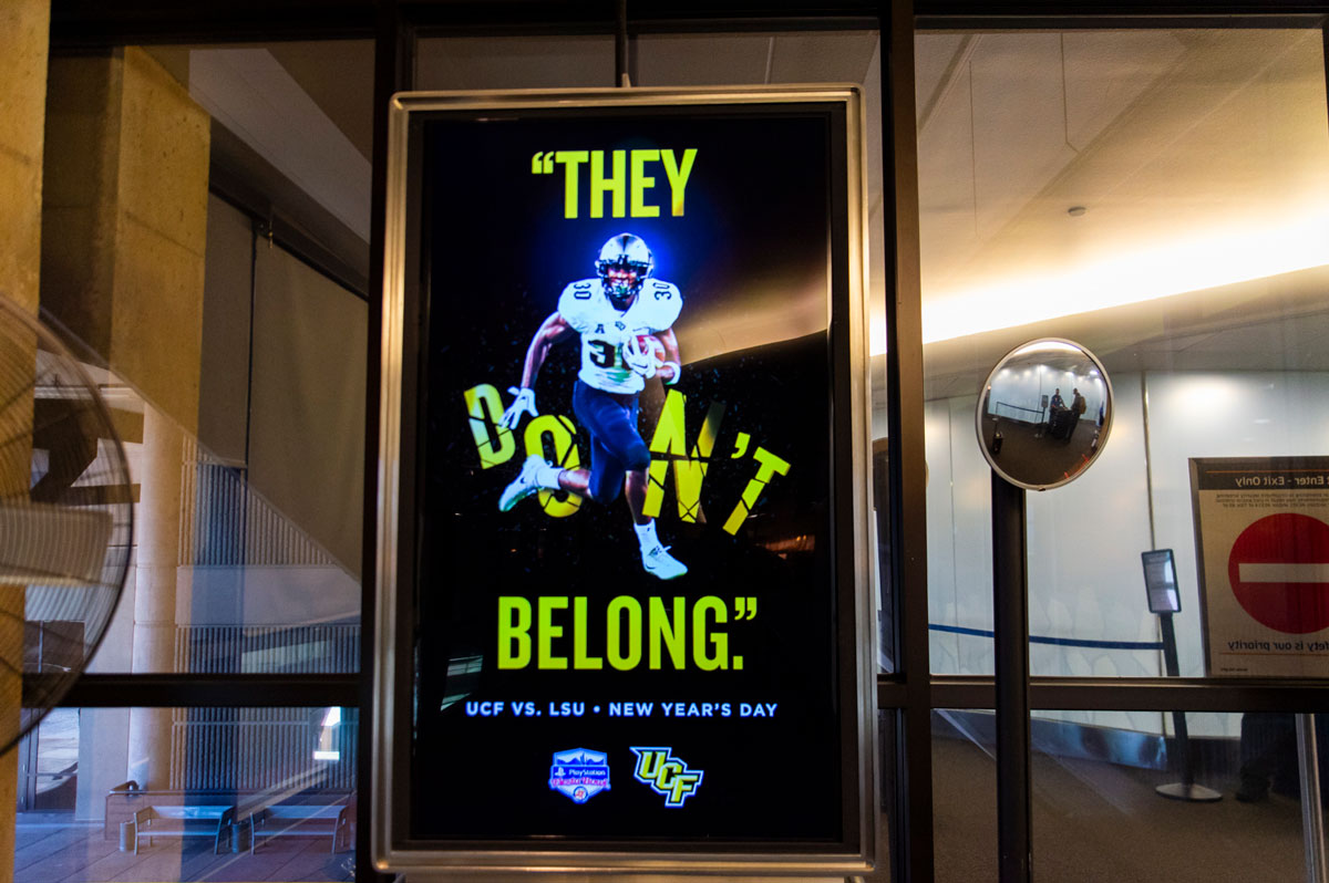 """sign that reads """"they don't belong"""" as a player breaks through the word """"don't"""""""