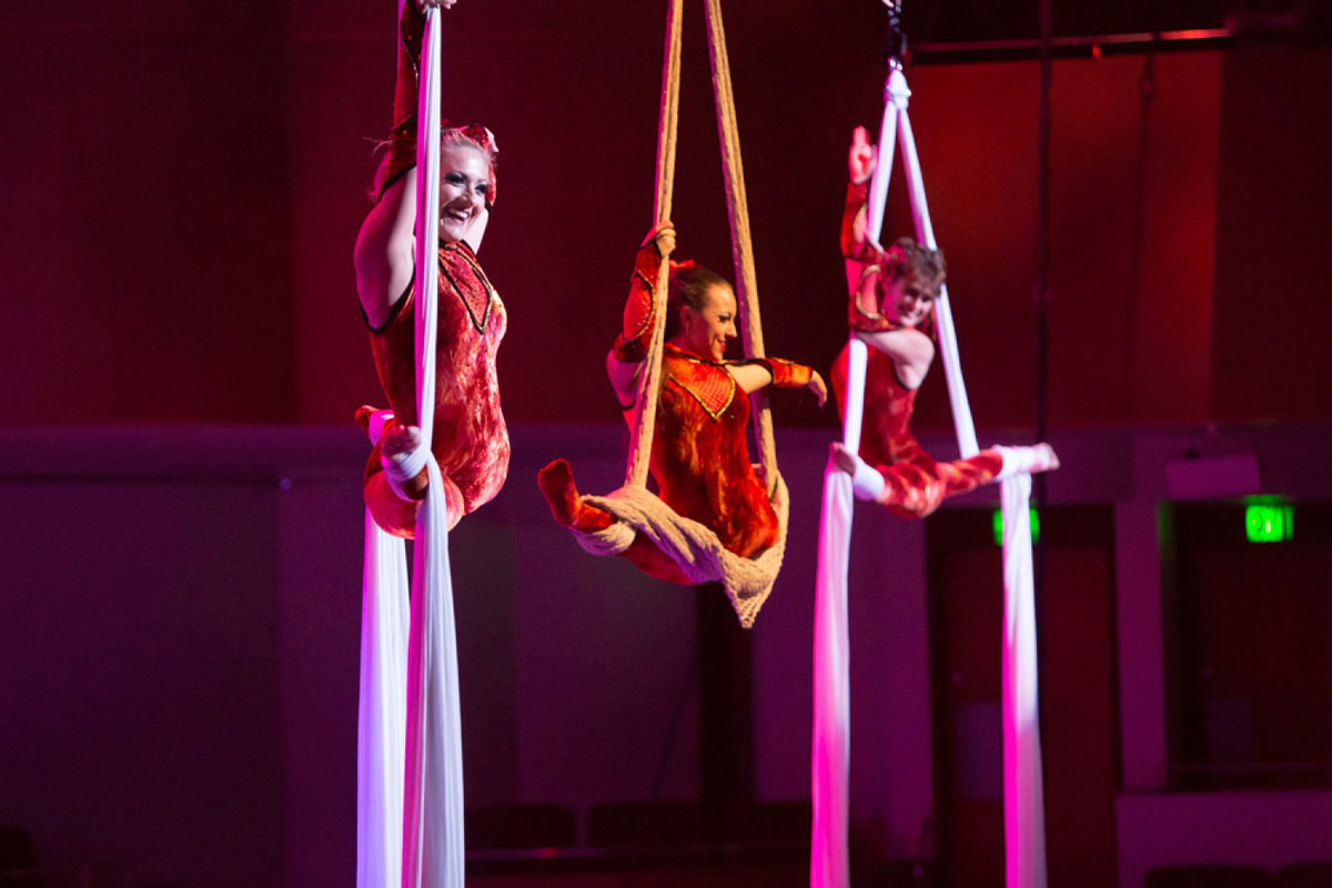 Three women wearing red costumes split midair while hanging from ropes