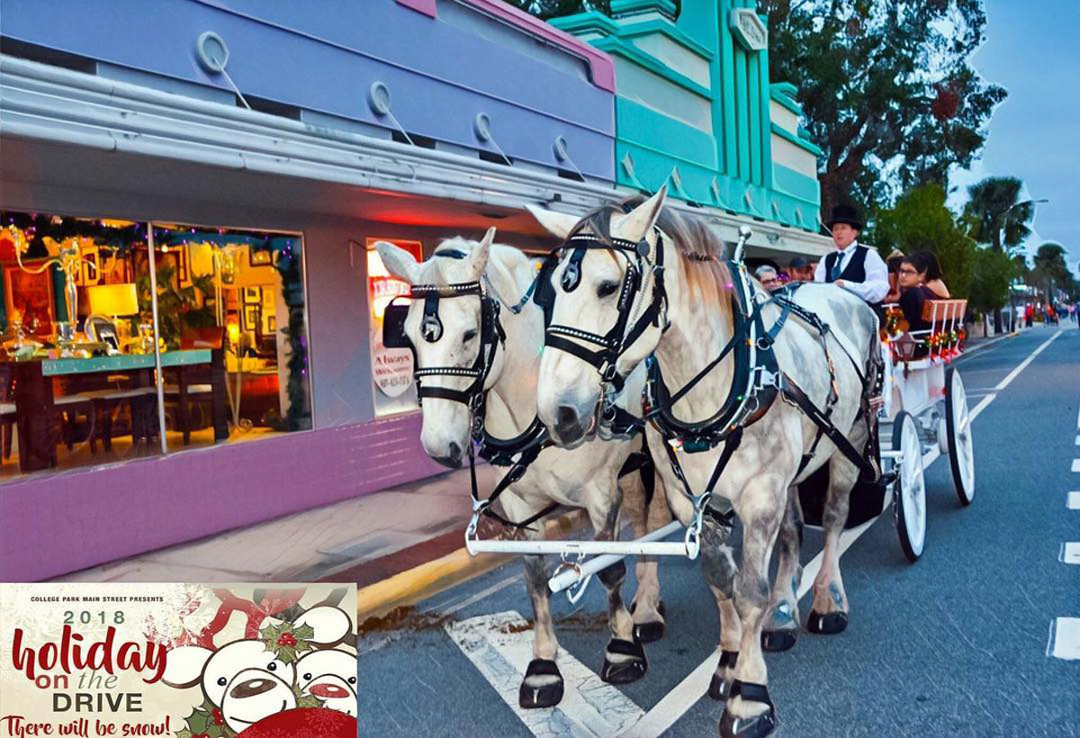 Two white horses pull a carriage of people down a paved road