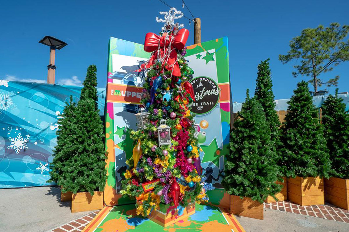 Colorful tall christmas tree in daylight with other non-decorated Christmas trees surrounding it