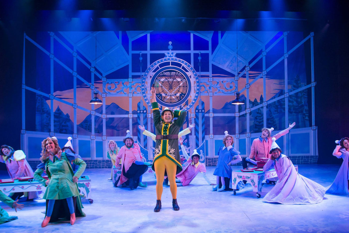 Theater stage with a man dressed like an elf in yellow pants and green jacket in the center standing and singing