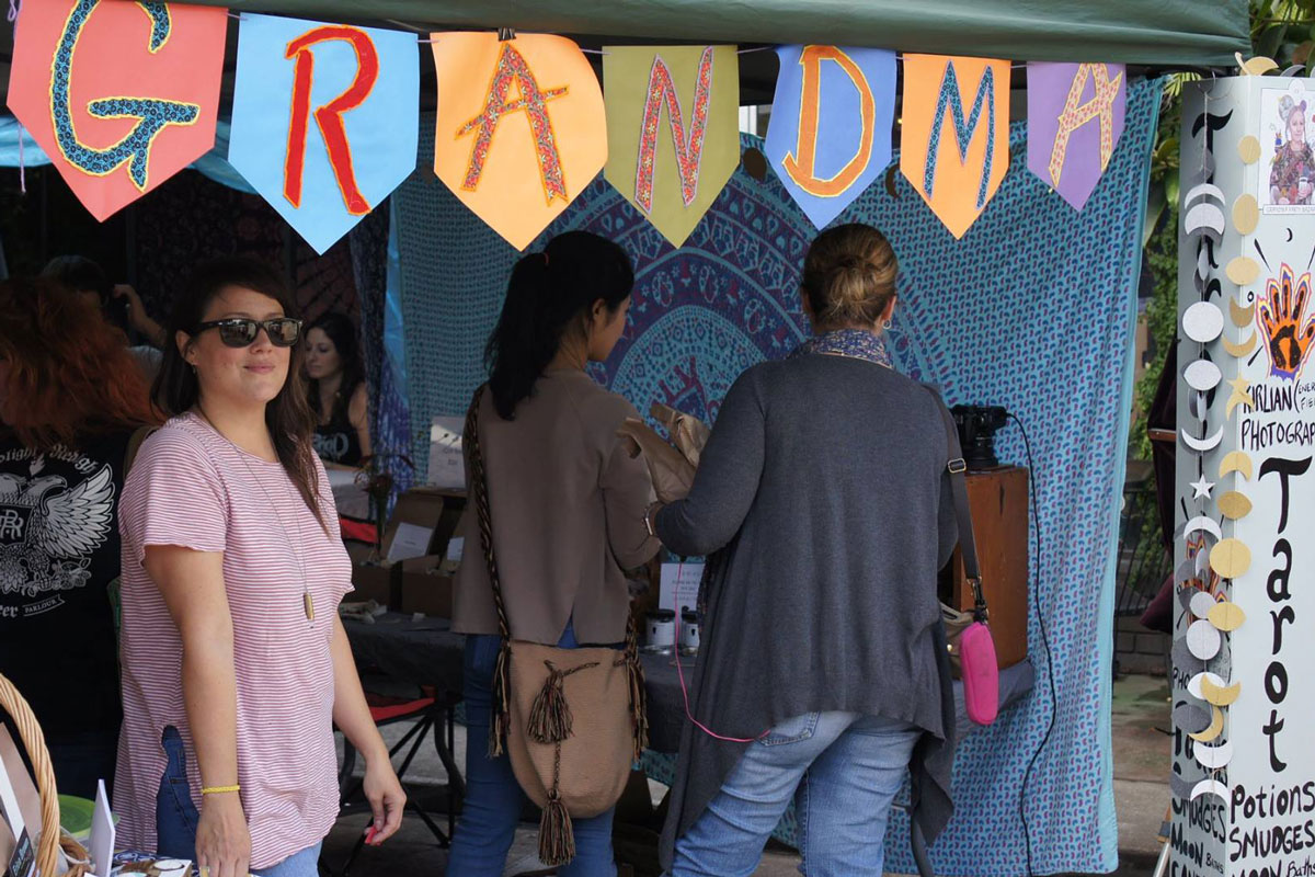 Three people shopping under a tailgate tent with a multi-colored banner hanging from the roof that reads Grandma