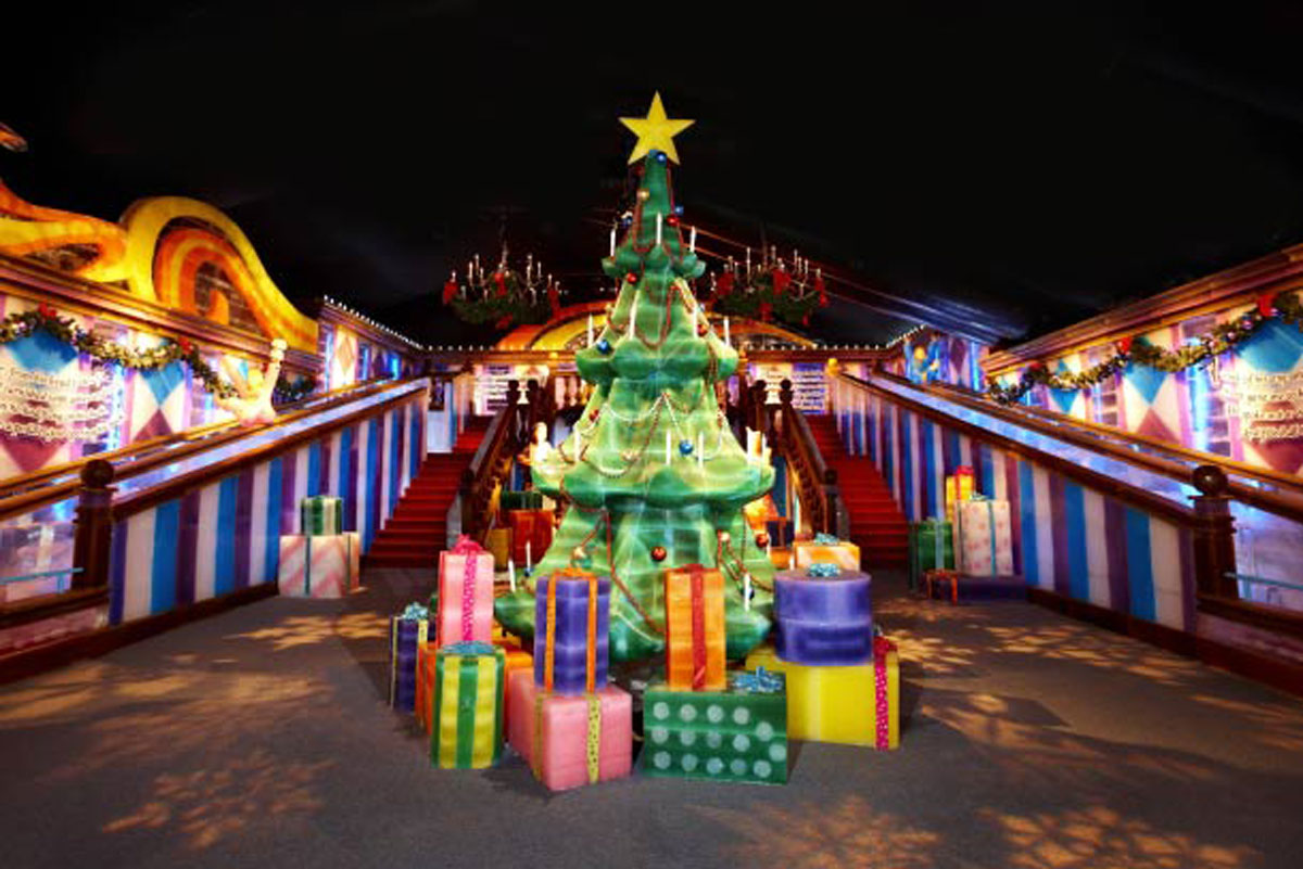 A green Christmas tree with a yellow star on top is surrounded by colorful presents, all made out of ice blocks