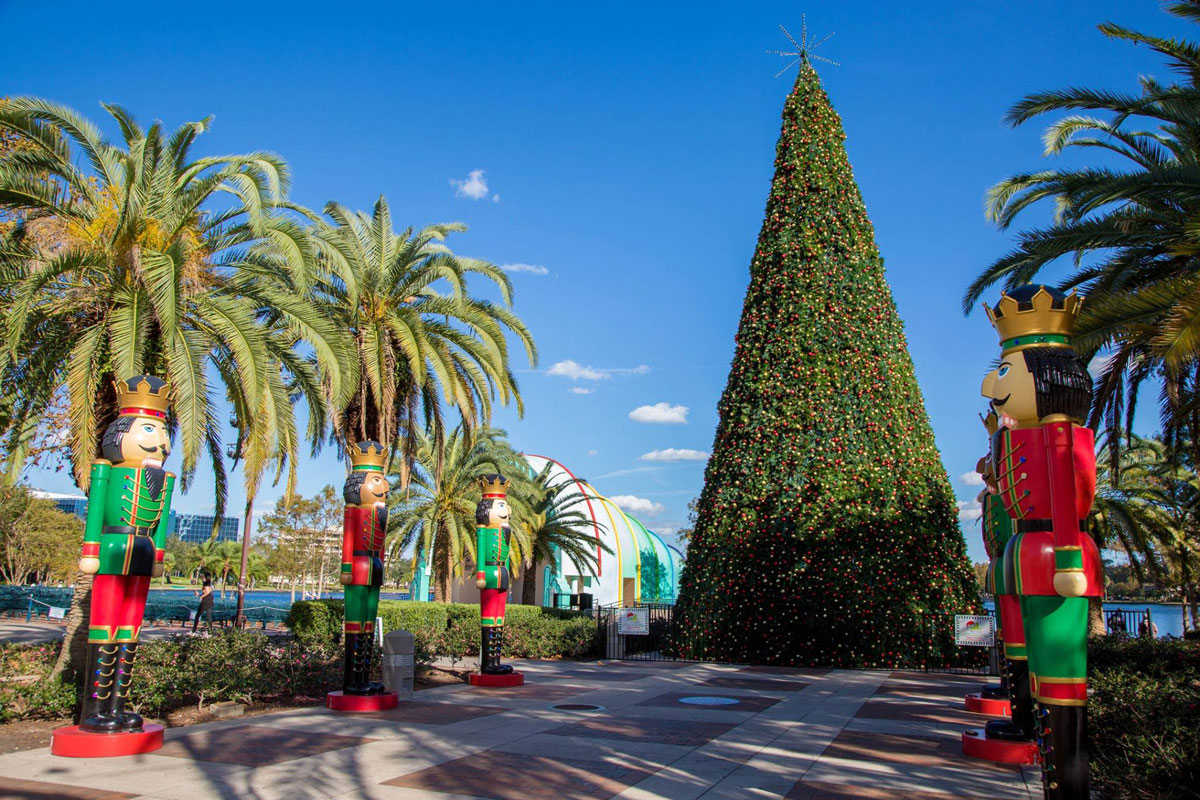 A giant Christmas tree is at the end of a path lined with red and green Nutcracker statues
