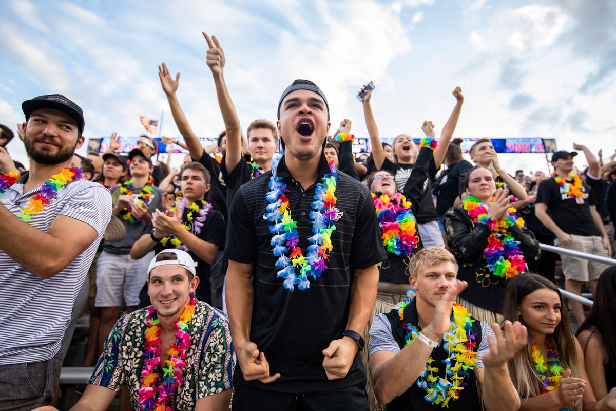 UCF fans cheer while wearing colorful leis