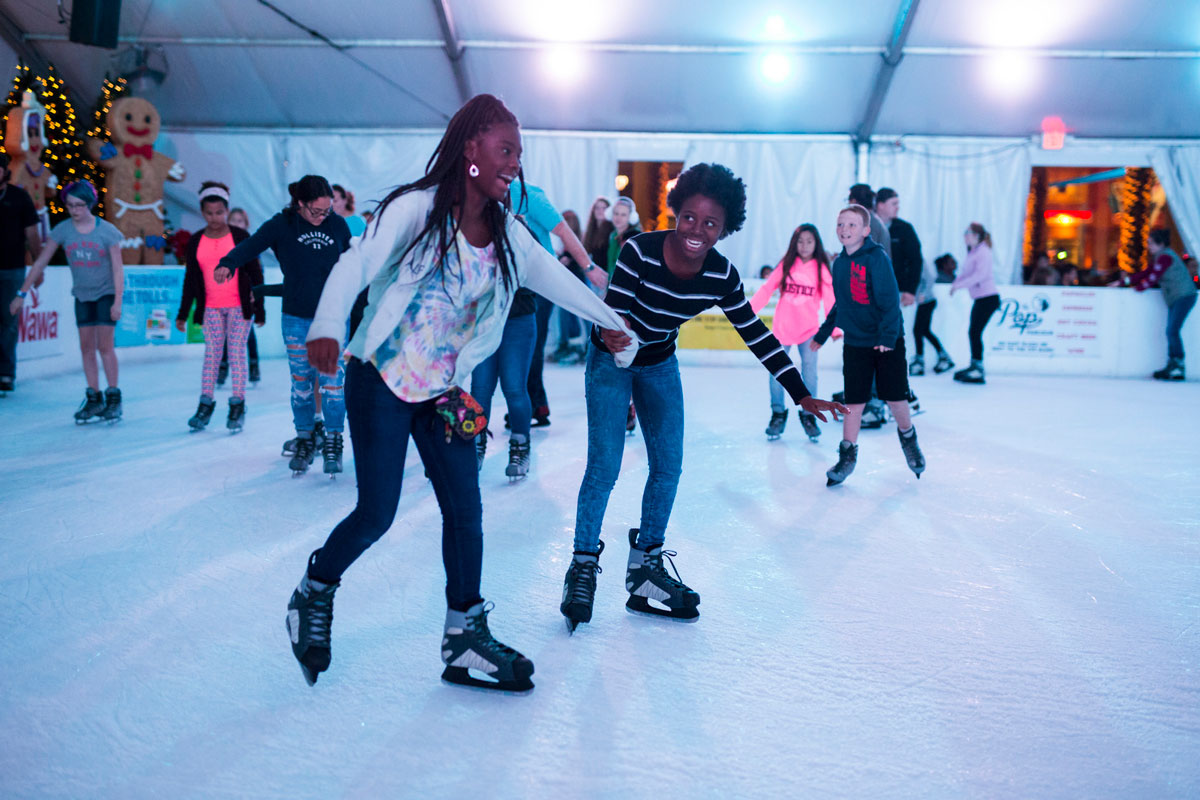 A group of people ice skate while holding hands