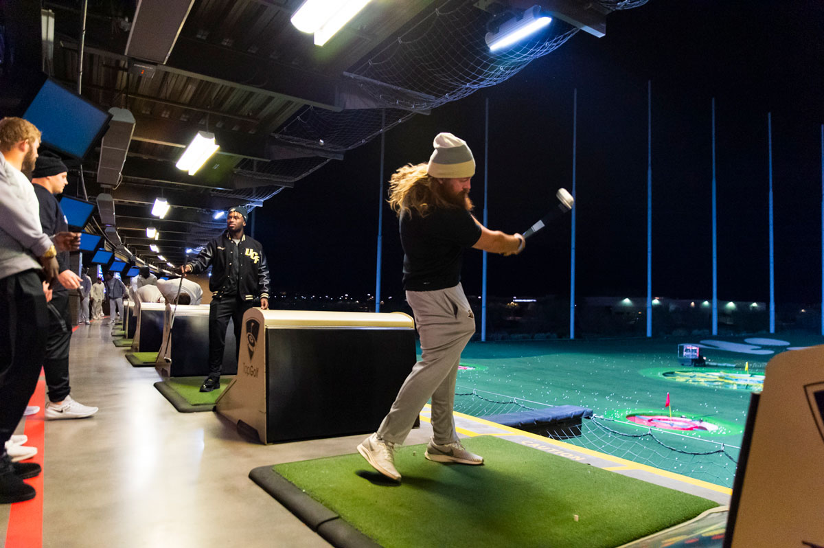 A man with long hair wearing a beanie and black shirt and khaki pants takes a golf swing at a driving range at night
