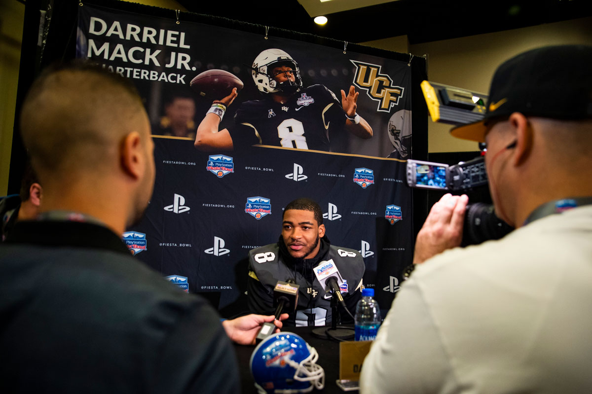 A football player sits in front of a media backdrop and answers questions into microphones from media members